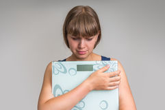 Frustrerad överviktig kvinna med våg Royaltyfria Foton