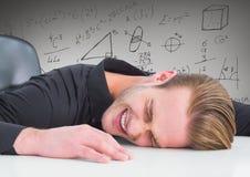 Frustrerad affärsman på skrivbordet mot gråa bakgrunds- och matematikdiagram Royaltyfri Foto