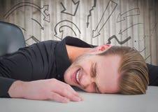 Frustrerad affärsman på skrivbordet mot oskarpa wood panel- och pildiagram Arkivfoton