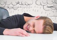 Frustrerad affärsman på skrivbordet mot vita wood panel- och regndiagram Fotografering för Bildbyråer