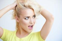 Frustrerad blond kvinna som mussing upp hennes långa hår Royaltyfri Bild
