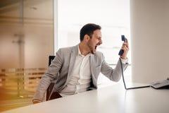 Frustrerad businessperson som skriker på telefonen royaltyfria foton