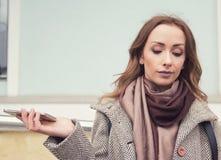 Frustrerad förargad kvinna med den stående yttersidan för mobiltelefon på gatan Arkivfoto