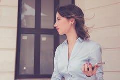 Frustrerad förargad kvinna med mobiltelefonanseende utanför lägenhetandelsfastighet Fotografering för Bildbyråer