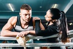Frustrerad grabb i boxningsring den härliga flickan stöttar den unga mannen royaltyfria bilder
