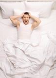 Frustrerad grabb som ligger i säng royaltyfria bilder