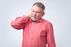 Frustrerad hög man i röd skjortainnehavhand på hans hals royaltyfri bild