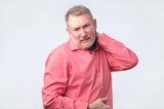 Frustrerad hög man i röd skjortainnehavhand på hans hals arkivbilder