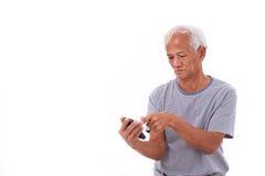 Frustrerad hög gamal man som har problem genom att använda den smarta telefonen Royaltyfri Fotografi