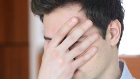 Frustrerad ilsken man, framsida som täckas med handen fotografering för bildbyråer