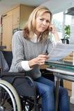 Frustrerad kvinna i rullstolläsningbokstav royaltyfri bild