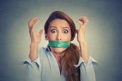 Frustrerad kvinna med det gröna mäta bandet runt om hennes mun Arkivbild