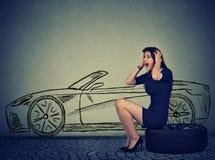 Frustrerad kvinna med det plana gummihjulet för bruten ner bil Arkivfoton