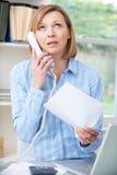 Frustrerad kvinna på telefonen i inrikesdepartementet Fotografering för Bildbyråer