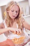Frustrerad kvinna som äter chiper Arkivfoto
