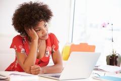 Frustrerad kvinna som arbetar på skrivbordet i designstudio royaltyfri bild