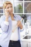 Frustrerad kvinna som kallar den rörmokareTo Fix Blocked vasken hemmastadd Arkivbild
