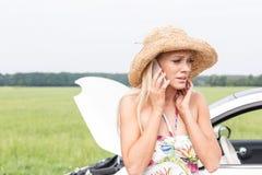 Frustrerad kvinna som ner använder mobiltelefonen med den brutna bilen Fotografering för Bildbyråer