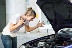 Frustrerad kvinna som ner ser den brutna bilmotorn Arkivbild