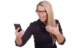 Frustrerad kvinna som ser henne som är mobil Royaltyfri Foto