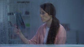 Frustrerad kvinna som ser på lungaröntgenstråle på den regniga dagen, obotlig sjukdom, cancer arkivfilmer
