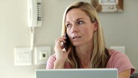 Frustrerad kvinna som skakar hennes huvud, medan hon är på telefonen arkivfilmer