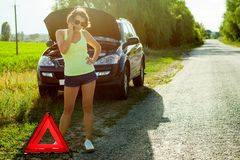 Frustrerad kvinnachaufför nära en bruten bil En bil på en landsro Arkivfoto