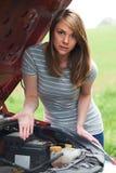 Frustrerad kvinnlig bilist med den brutna ner bilen arkivfoto