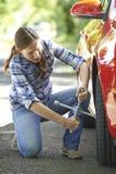 Frustrerad kvinnlig chaufför With Tyre Iron som försöker till ändringshjulet royaltyfri fotografi