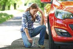 Frustrerad kvinnlig chaufför With Tyre Iron som försöker till ändringshjulet royaltyfri foto