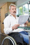 Frustrerad man i hemmastadd läsningbokstav för rullstol arkivfoton
