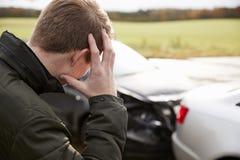 Frustrerad man med den skadade bilen efter olycka royaltyfri foto