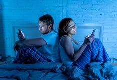 Frustrerad man och hemfallna kvinnapar genom att använda mobiltelefoner i säng på natten som ignorerar sig arkivfoton