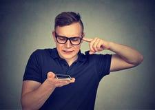 Frustrerad man som använder en smart funktion för telefonstämmaerkännande på linje royaltyfri foto
