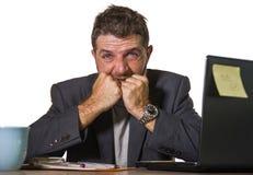 Frustrerad man som arbetar på det desperata skrivbordet för kontorsdator och den förkrossade känslarubbningen som in lider fördju arkivbilder