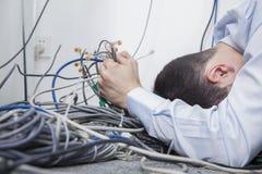 Frustrerad man som ligger försöka ner att figurera ut och sortera datorkablar Royaltyfri Fotografi