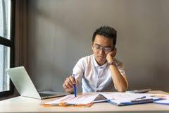 Frustrerad man som sitter på det arbetande skrivbordet med bärbara datorn och dokumentet arkivbilder