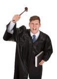 Frustrerad manlig domare med auktionsklubban och boken Fotografering för Bildbyråer