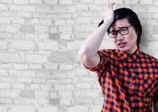 Frustrerad millennial man mot den vita tegelstenväggen Arkivfoton
