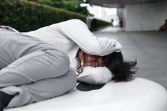 Frustrerad stressad ung asiatisk affärsman som ner ligger och känner sig sviken eller evakuerad med jobb royaltyfri bild