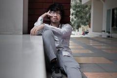 Frustrerad stressad ung asiatisk känsla för affärsmannen försökte eller bekymmer med jobb royaltyfri bild