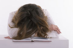Frustrerad student som sover på boken Arkivfoto