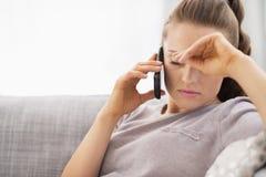 Frustrerad talande mobiltelefon för ung kvinna Royaltyfri Bild