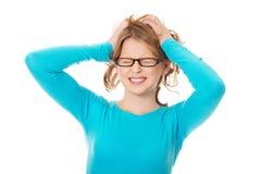 Frustrerad tonårs- kvinna som drar hennes hår Arkivfoto