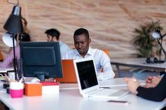 Frustrerad ung afrikansk entreprenör med den ledsna grimasen som är främst av hans bärbar dator i regeringsställning Arkivfoton