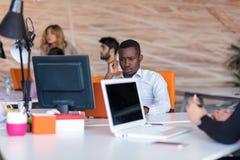 Frustrerad ung afrikansk entreprenör med den ledsna grimasen som är främst av hans bärbar dator i regeringsställning Royaltyfri Foto