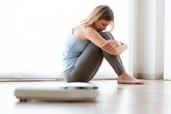 Frustrerad ung ledsen kvinna, når att ha sett hennes vikt på skalan hemma royaltyfri fotografi