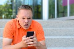 Frustrerad ung man som gör en gest på hans mobiltelefon Arkivfoto