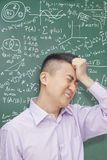 Frustrerad ung student framme av svart tavla med matematiklikställande som rymmer huvudet Royaltyfri Fotografi