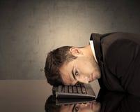 Frustrerade affärsmans huvud på tangentbordet Arkivbild